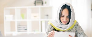 Woman reading her tablet in her home office