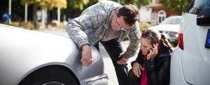 Middle-aged man and young adult woman examining their cars after an accident