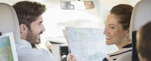 Parents sitting in the front seat of the car, checking a map and talking with their kids