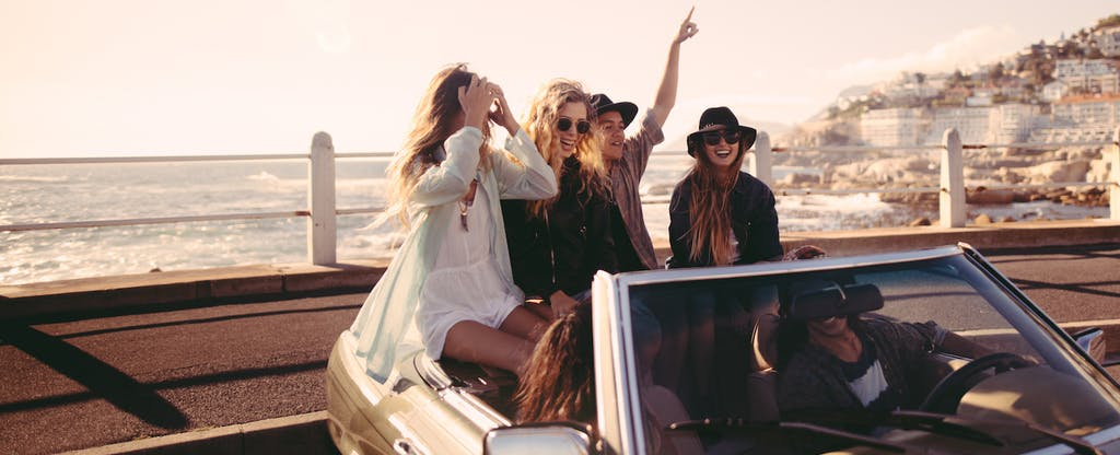 Group of young adult friends smiling and celebrating in a convertible parked close to the beach
