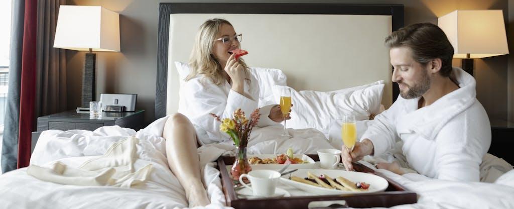 Couple in bathrobes enjoying breakfast in bed in luxury hotel