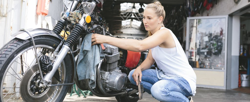 Young woman cleaning motorcycle