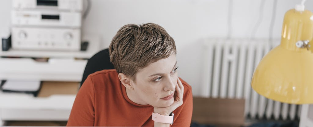 Woman sitting at her desk and thinking, with her head resting in her hand