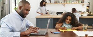 African American father working at laptop at kitchen table while his young daughter sits next to him coloring