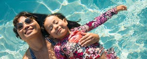A woman and her daughter floating in a pool