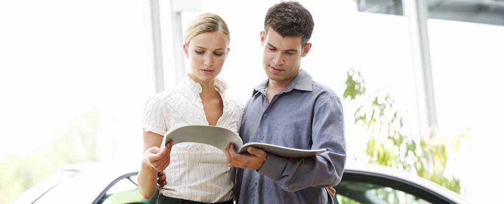 Couple at a car dealership looking through paperwork