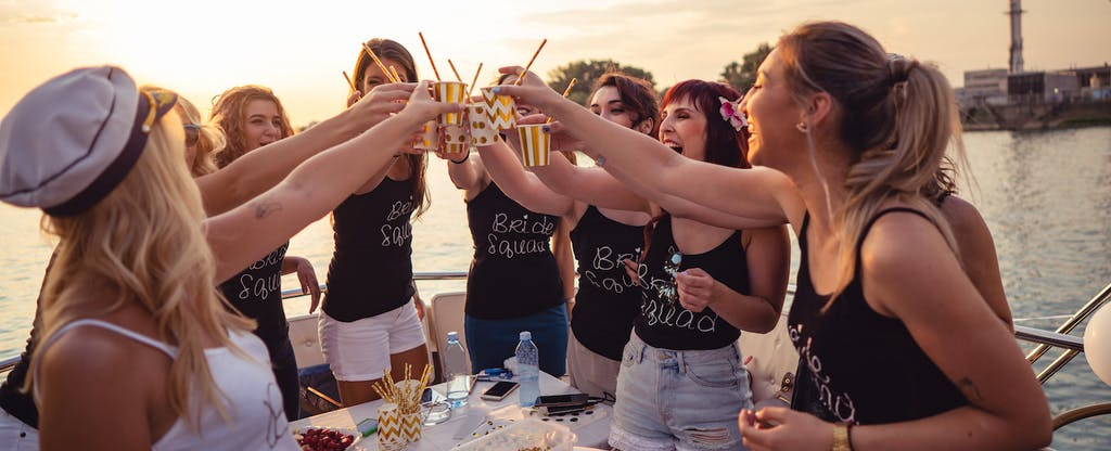 Ladies celebrating bachelorette party outside on a boat