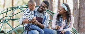 Young African American parents holding their son at a playground