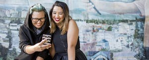 Two smiling Asian women posing for cell phone selfie