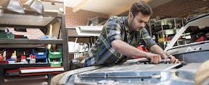 Mechanic fixing car engine in auto repair shop