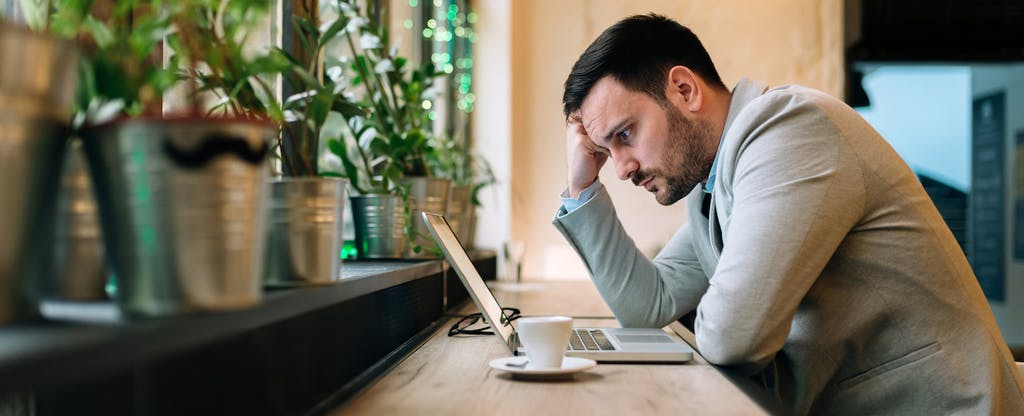 Worried man looking at laptop screen while sitting in coffee shop