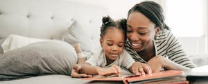 Mother reading to her toddler daughter in bed