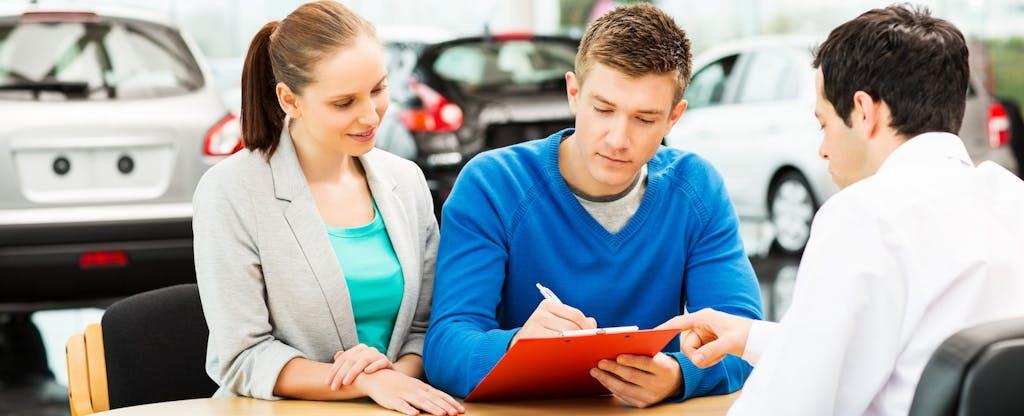 Couple filling out vehicle registration paperwork at car dealership