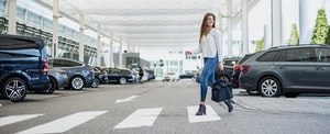 Young Woman With Bag Crossing Street