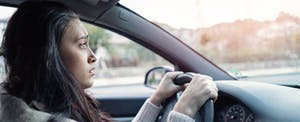 Concerned woman driving her car