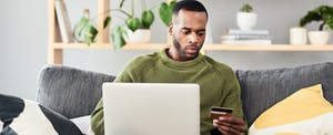 Young man sitting on sofa at home with laptop and holding a credit card