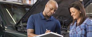 Mechanic explains vehicle repairs to customer in auto repair shop