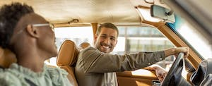 Man driving a car and smiling at a woman in the passenger seat