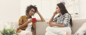 Two women sitting on a couch and having a conversation