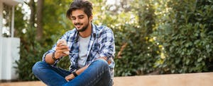Young adult male sitting on the ground and texting on a mobile phone