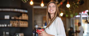Woman standing in a coffee shop, smiling