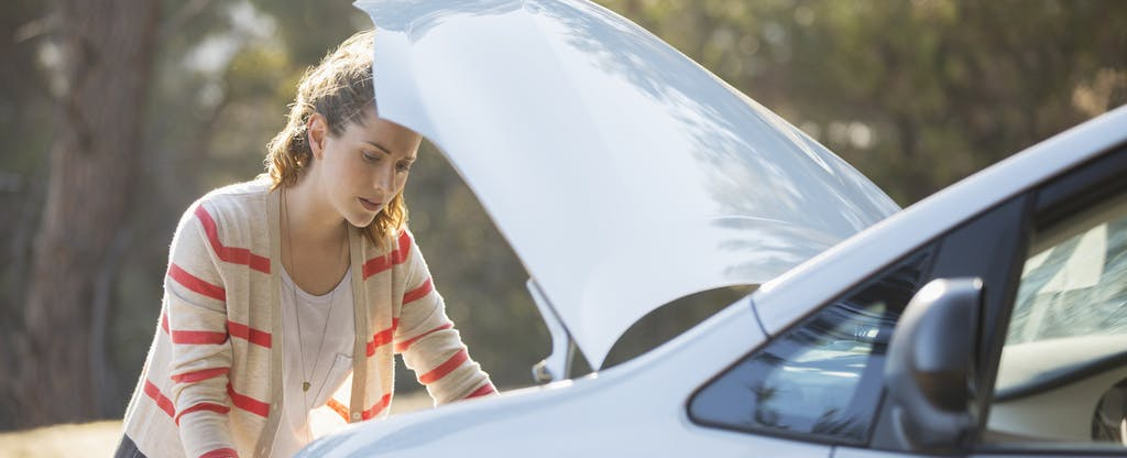 Woman looking under the hood of her car