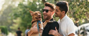 Two men smiling with their dog as while they stand outside