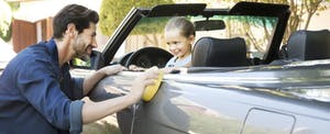 Father polishing convertible with smiling young daughter sitting in the front seat