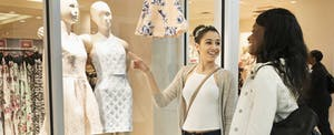 Two women standing outside a store window and looking at the mannequins