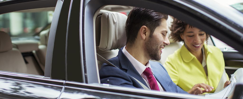 A man and a woman looking over sales paperwork while sitting in a new car