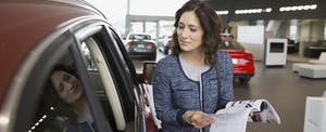 Woman with brochure in car dealership showroom