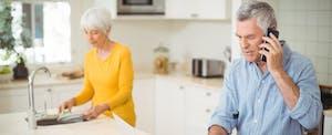Senior man talking on mobile phone while woman washing plate in kitchen