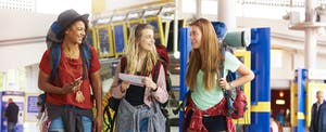 Three female friends in the airport going on a backpacking trip