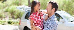 Father holding daughter outdoors with car in background