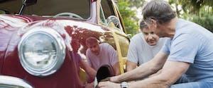 Two older men kneeling in front of the wheel of a red vintage car