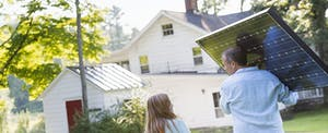 Man carrying a solar panel and talking to his young daughter