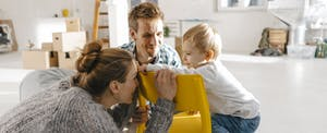 Mom and dad playing with their toddler child as they're working on a home renovation
