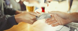 Woman presenting her prepaid card to pay at a restaurant bar