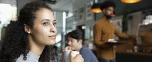 Woman sitting in a cafe, holding a cup of coffee and thinking