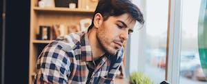 Man sitting at a cafe, looking at his phone