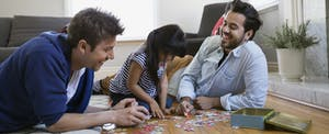 Same sex male couple and daughter assembling jigsaw puzzle in their living room