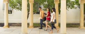 A group of 3 students walking together on campus