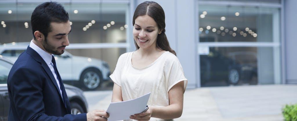 Woman doing a car title transfer at car dealership
