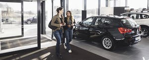 Two women walking into a car dealership, ready to shop for a new car