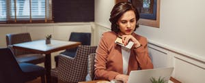 Woman sitting at her computer, holding her credit card and phone