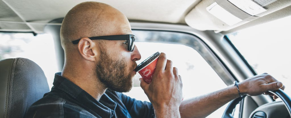 Man driving a car, sipping from a cup of coffee