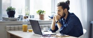 Man with laptop sitting at kitchen table researching personal loans with bad credit