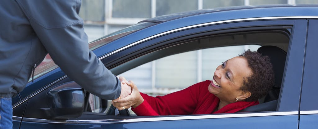 Woman sitting in the driver's seat of her car, shaking hands with a man standing outside of the car