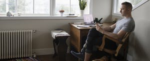 Man sitting at his desk and reading off of his phone