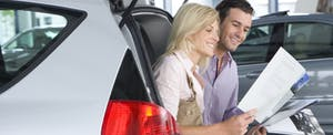 Couple looking at new car brochure and thinking about how to negotiate a car lease